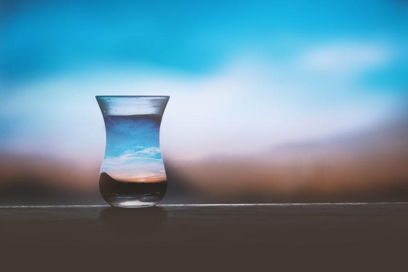 Ein Wasserglas vor einem Sonnenuntergang. Der Himmel bricht sich im Wasser.