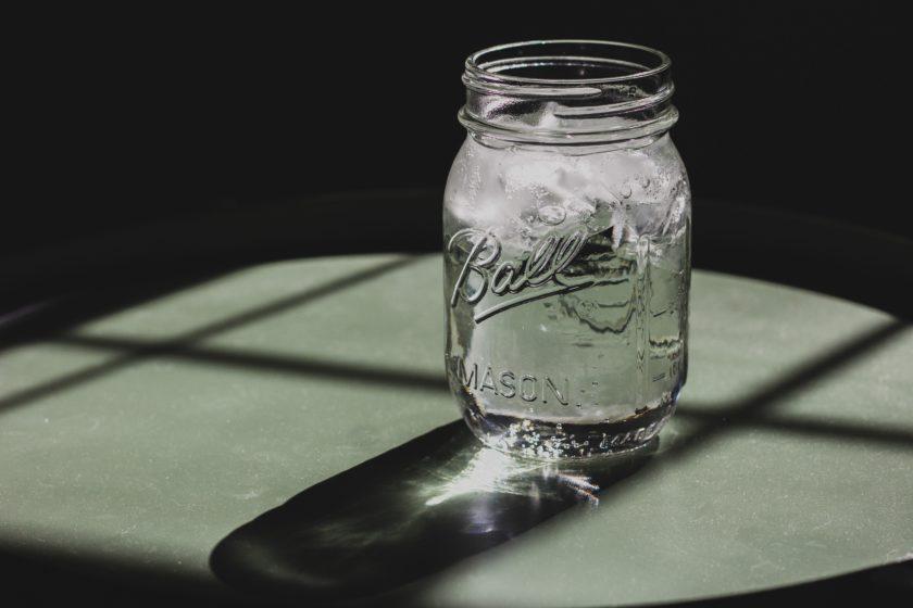 Wasserglas auf Tisch in der Sonne
