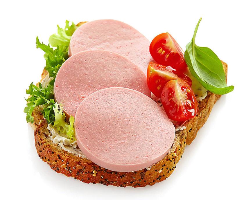 Brot mit Fleischwurst, Salat, Tomate und Basilikum zur Veranschaulichung von modernem verarbeitetem Essen.