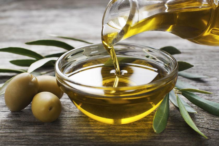 Olivenöl, das langsam von Karaffe in Schälchen gegossen wird