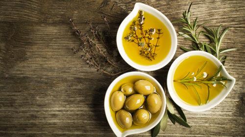Olivenöl mit frischen Oliven in schönen Schälchen auf Tisch