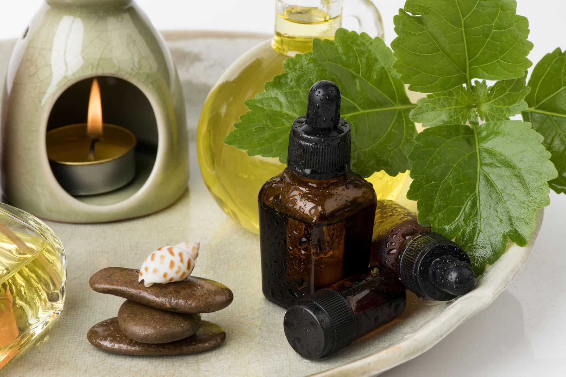 Patchouliöl in kleinen Pipetten-Flaschen und Duftlampe