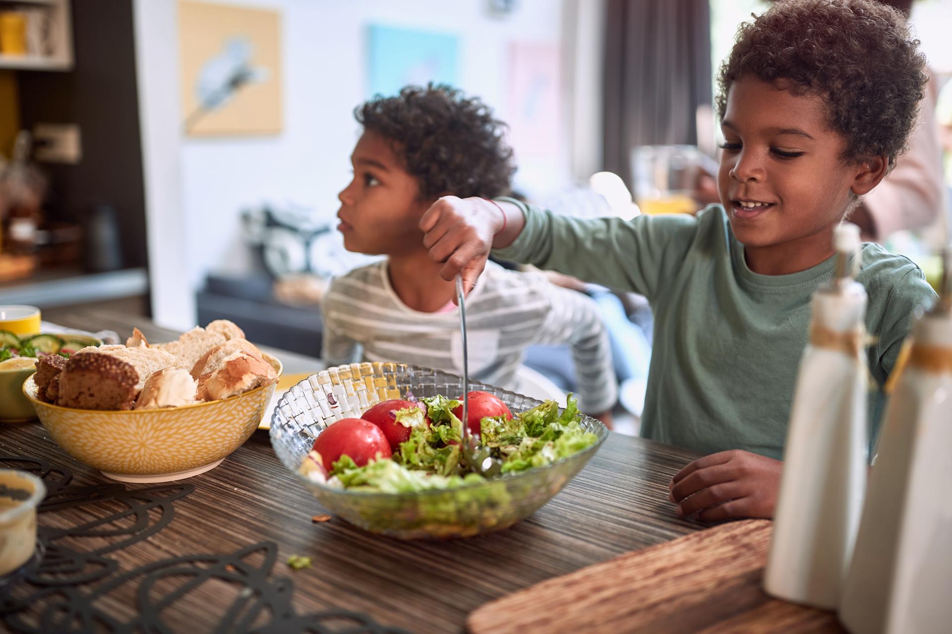 Kleine Kinder die intuitiv Salat und Gemüse essen und schlank sind.